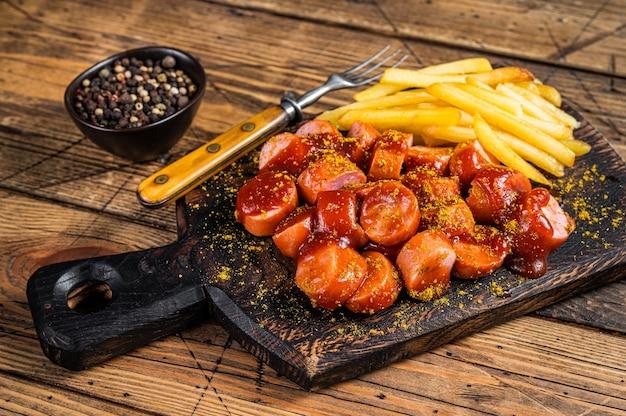 Saucisses au curry wurst avec frites sur une planche de bois