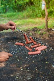 Saucisses au grill sur le feu. la main de l'homme enlève les saucisses du gril