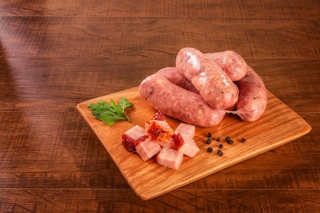 Saucisses de bacon brésilien cru sur la planche de bois avec des cubes de bacon et d'épices