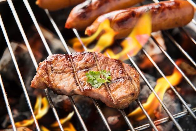 Saucisses barbecue et viande sur le gril.