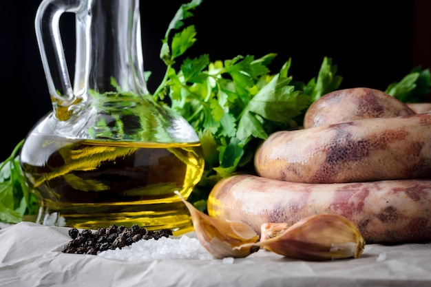Saucisses à base de viande, d'épices et d'huile d'olive sur un fond sombre