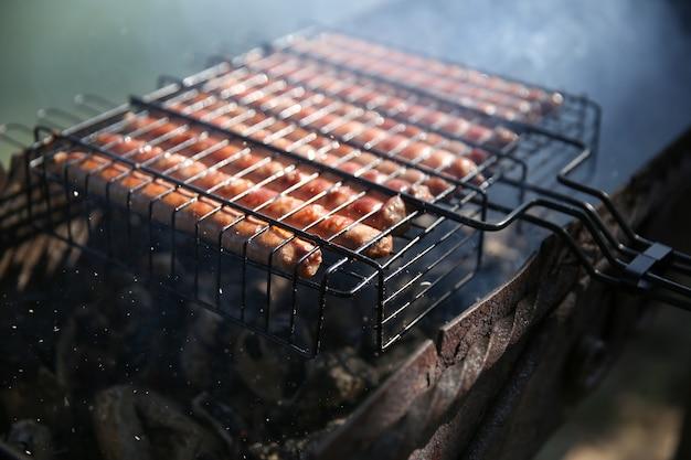 Saucisses bavaroises avec de la fumée sur le gril close up