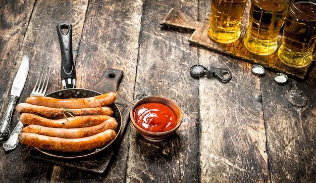 Saucisses à la bière froide et sauce sur table en bois.