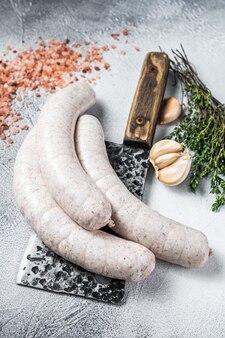 Saucisses blanches traditionnelles bavaroises sur un couperet à viande. fond blanc. vue de dessus.