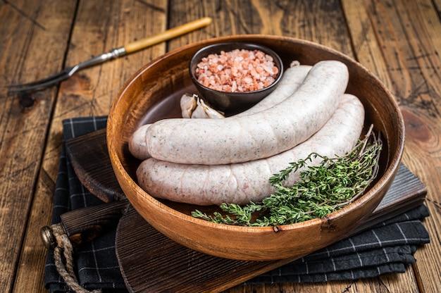 Saucisses blanches traditionnelles de munich crues dans une assiette en bois avec des herbes. fond en bois. vue de dessus.