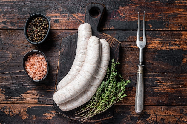 Saucisses blanches traditionnelles de munich sur une planche de bois avec du thym. fond en bois foncé. vue de dessus.