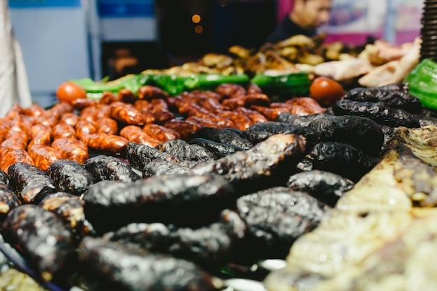 Saucisses et boudins noirs grillés au barbecue.