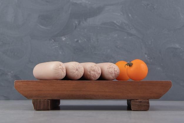 Saucisses bouillies fraîches et tomates cerises sur planche de bois.