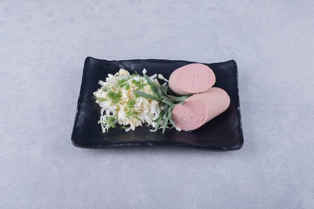 Saucisses bouillies et fromage sur plaque noire.