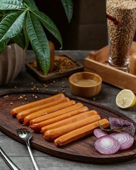 Saucisses bouillies garnies d'oignon rouge et de citron sur un plateau en bois