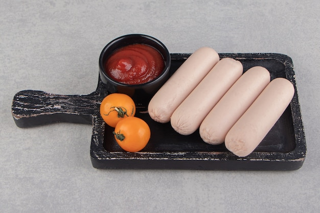 Saucisses bouillies avec ketchup et tomates sur tableau noir.