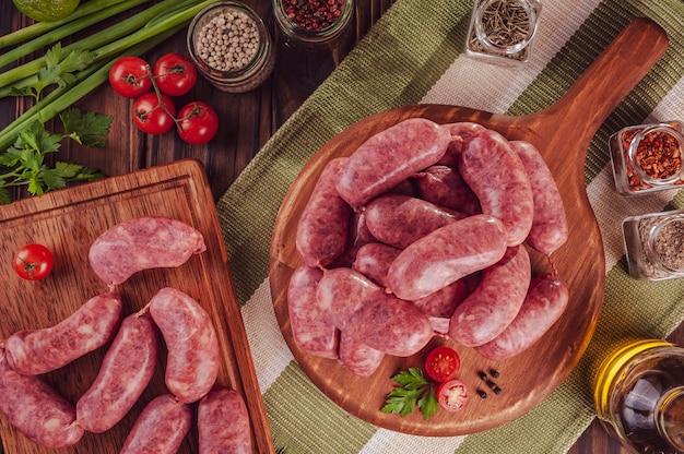 Saucisses brésiliennes crues sur la planche de bois avec des ingrédients