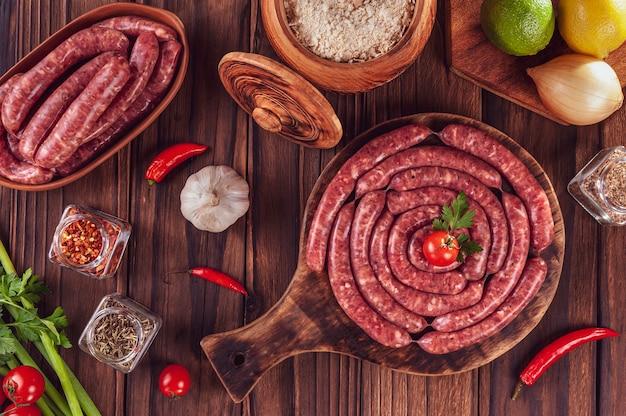 Saucisses brésiliennes minces crues sur la planche de bois avec des ingrédients linguica toscaninha