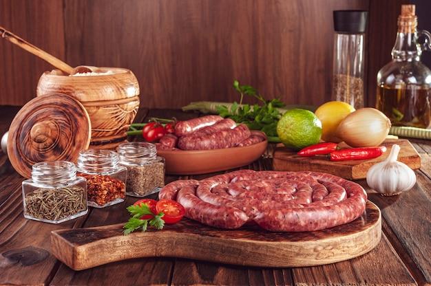 Saucisses brésiliennes minces crues sur la planche de bois avec des ingrédients