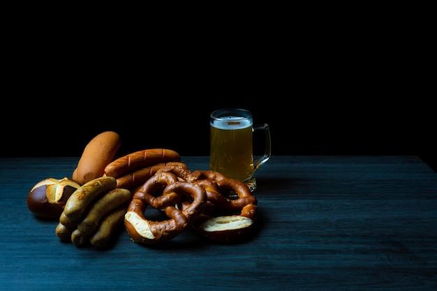 Saucisses de bretzels et bière sur table en bois et style de nourriture sombre oktoberfest