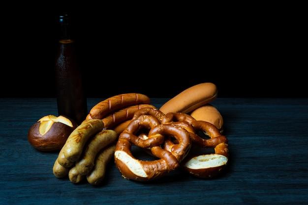 Saucisses et bretzels oktoberfest avec de la bière sur une table en bois de style alimentaire sombre
