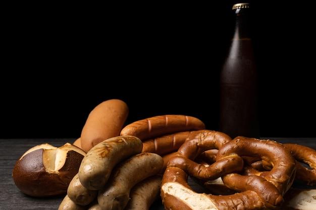 Saucisses et bretzels oktoberfest avec bouteille de bière et fond sombre