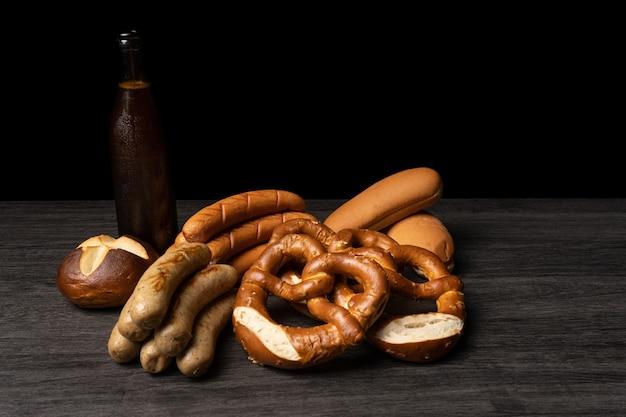 Saucisses et bretzels oktoberfest avec bouteille de bière et table de fond sombre