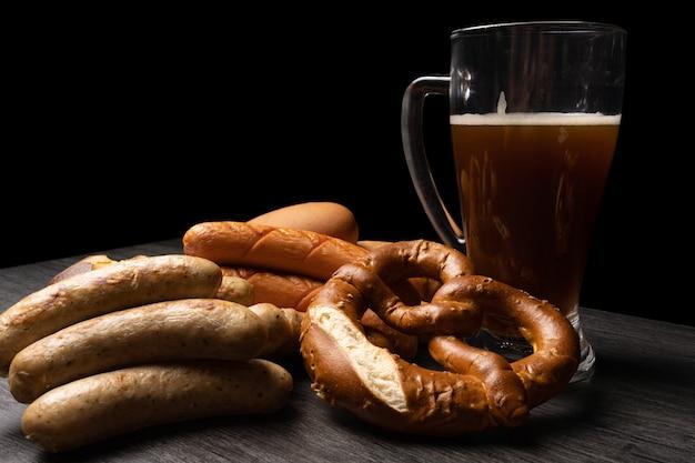 Saucisses et bretzels oktoberfest avec pot de bière et table texturée sur fond sombre