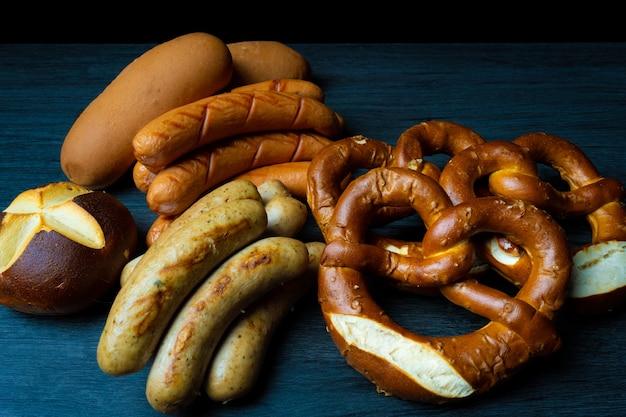 Saucisses et bretzels oktoberfest de style alimentaire sombre sur table en bois