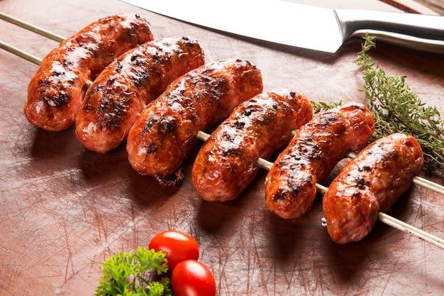 Saucisses sur la broche du barbecue sur l'espace en bois