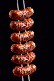 Saucisses sur la broche du barbecue sur l'espace noir