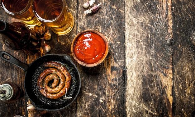 Saucisses chaudes avec bière froide sur table en bois.