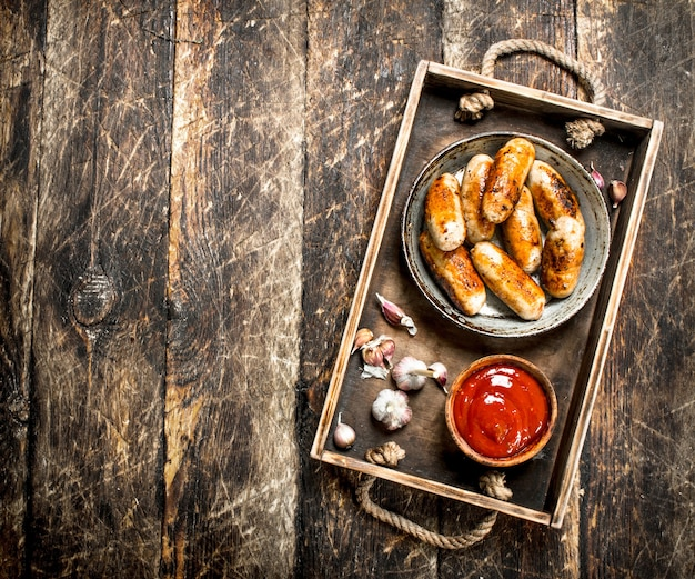 Saucisses chaudes à la sauce tomate. sur un fond en bois.