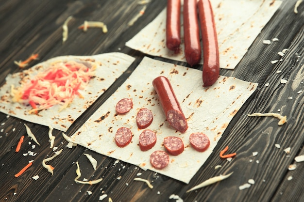Saucisses, chou mariné et pain pita sur fond de bois.