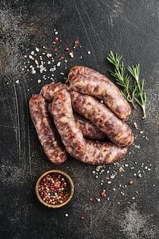 Saucisses crues ou bratwurst sur papier parchemin et ingrédients pour la cuisson. vue de dessus avec espace de copie sur table en pierre.