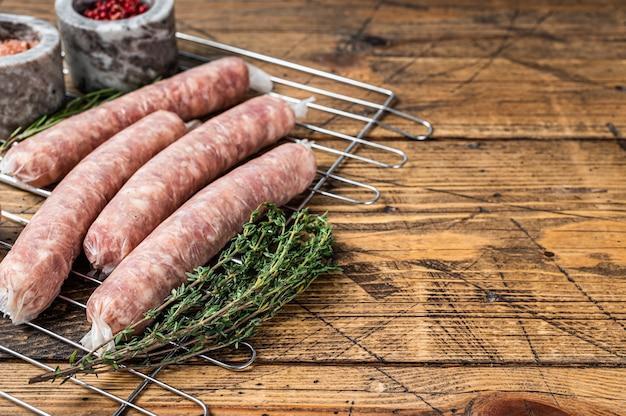 Saucisses crues - bratwurst avec de la viande de porc sur un gril. fond en bois. vue de dessus. espace de copie.