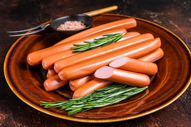Saucisses crues frankfurter dans une assiette rustique avec des herbes