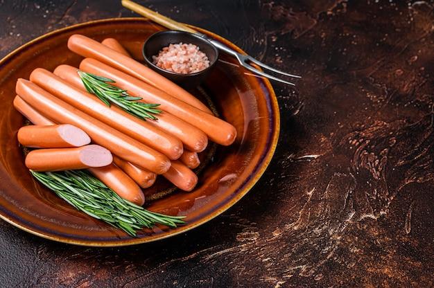 Saucisses crues wiener dans une assiette rustique avec des herbes