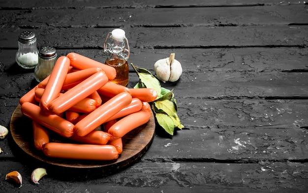 Saucisses cuites aux épices et assaisonnements. sur fond rustique noir.