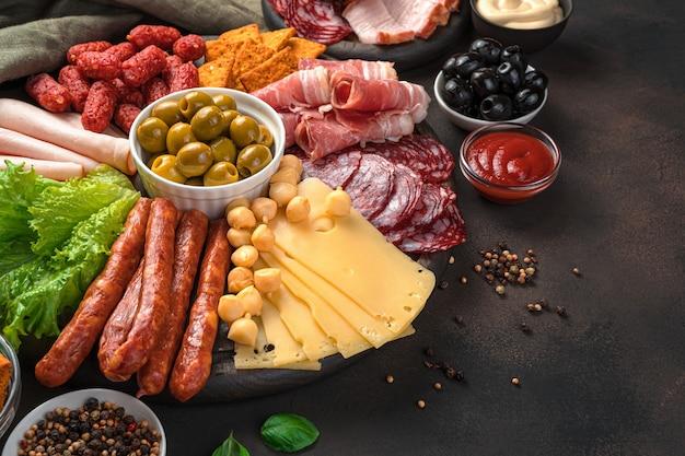Saucisses de différents types, viande fumée, fromage et olives sur un bureau marron avec espace pour copier.