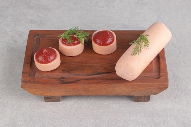 Saucisses faites maison bouillies et ketchup sur planche de bois.