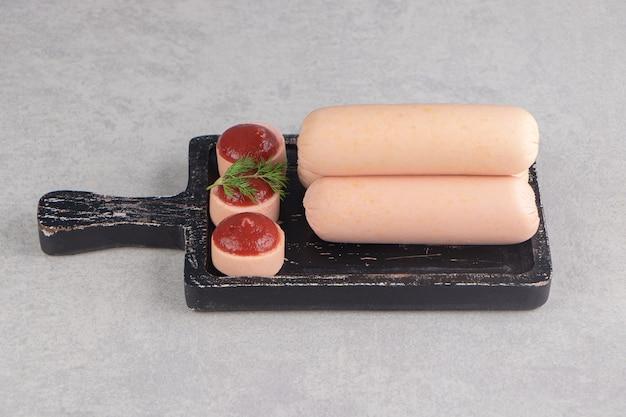 Saucisses faites maison bouillies et ketchup sur tableau noir.