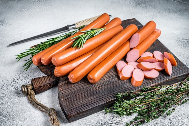 Saucisses de frankfurter crues allemandes sur une planche de bois