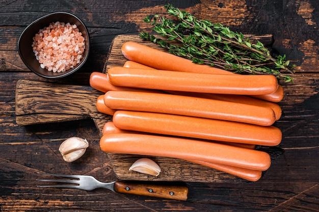 Saucisses frankfurter sur planche à découper en bois