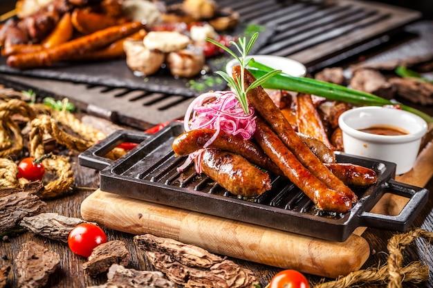 Saucisses frites assorties sur un gril sur une planche de bois.