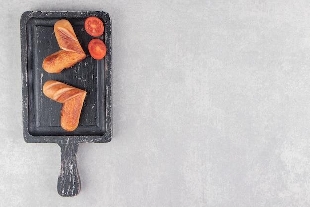 Saucisses frites aux tomates sur tableau noir.