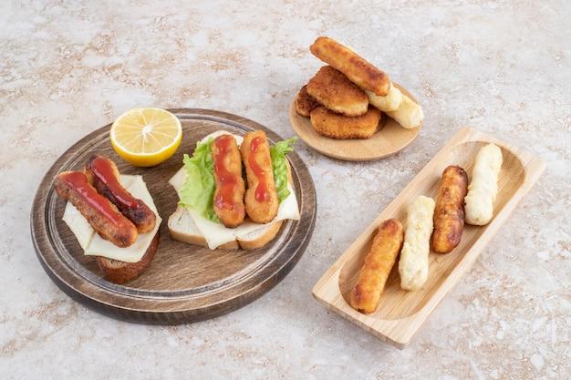 Saucisses frites et bâtonnets de fromage sur des toasts de sandwich avec un citron.