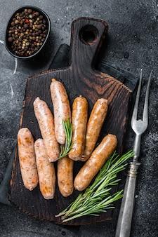 Saucisses frites bratwurst ou hot dogs sur une planche de bois. fond noir. vue de dessus.