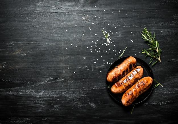 Saucisses frites dans une casserole avec du romarin. sur le tableau noir.