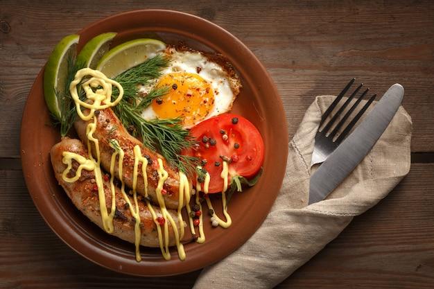 Saucisses frites avec des épices, des légumes et des verts.