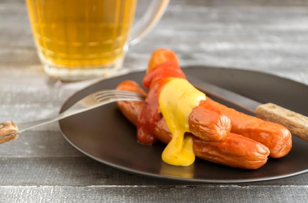 Saucisses frites à la moutarde et au ketchup sur une plaque noire.