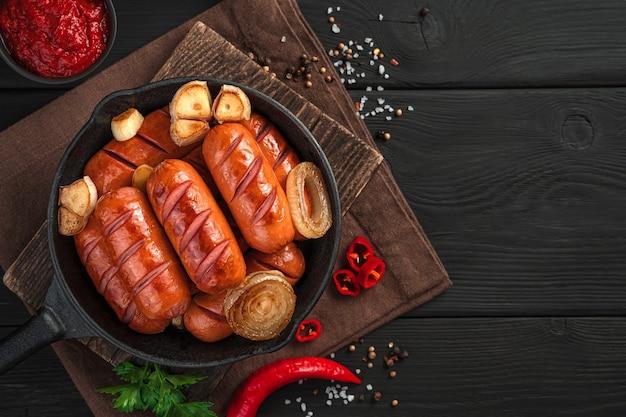 Saucisses frites avec oignons et ail dans une poêle