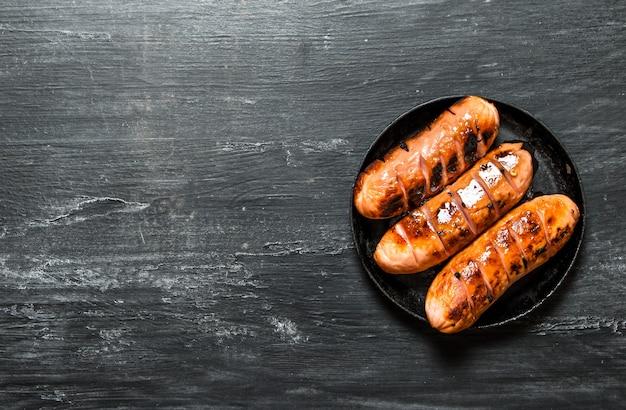 Saucisses frites sur une poêle. sur fond rustique noir.