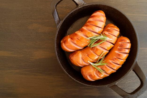 Saucisses frites sur une poêle en fonte. sur le tableau