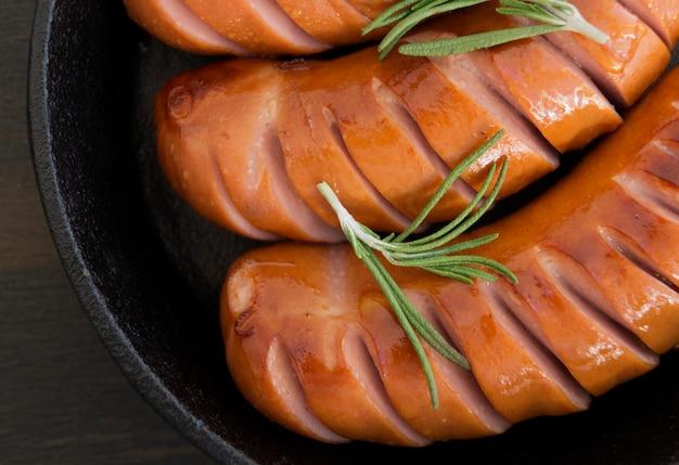 Saucisses frites sur une poêle en fonte.